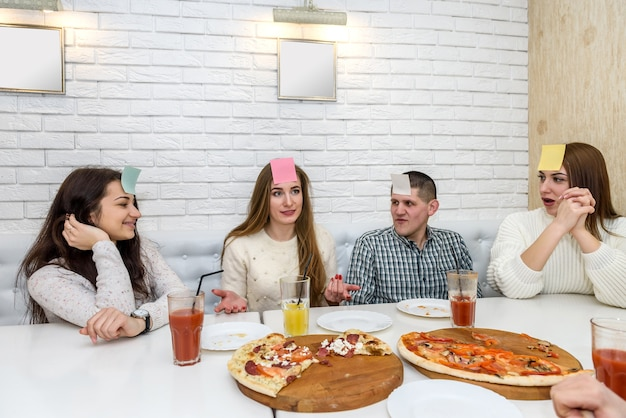 In the cafe, friends eat pizza, chat and play games