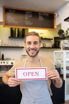 カフェは営業しています。看板を保持しているエプロン立っている傾いたバーカウンターで幸せな楽観的な若い成人男性カフェで開く