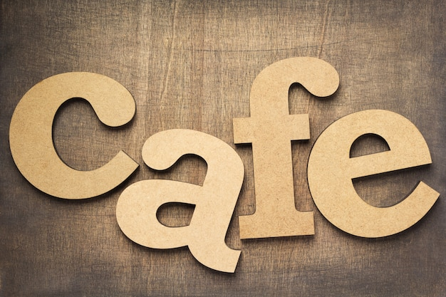 Cafe letters at old wooden background, top view