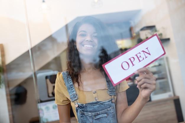 カフェオープン。赤い碑文が開いている白い看板を示すカフェ内のガラスの後ろに長い髪の笑顔の若い女性