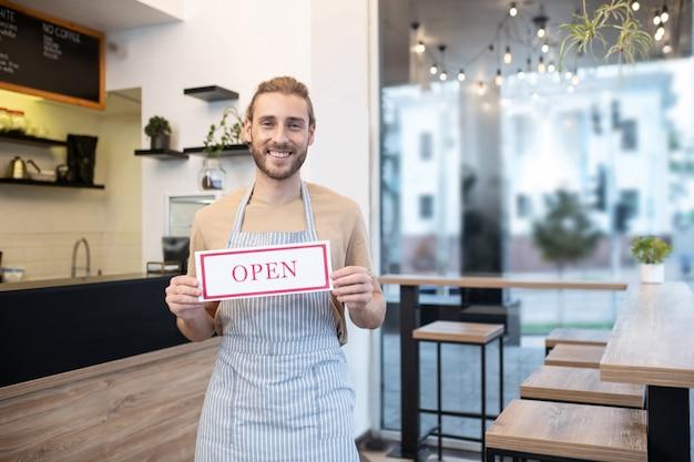 カフェオープン。カフェで公然と立っている碑文と看板を保持しているエプロンで若い大人の笑顔の男