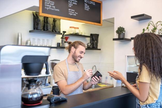 카페, 주문. 카운터와 여자 주문 뒤에 유리에 마커로 쓰는 앞치마에 세심한 남자 미소