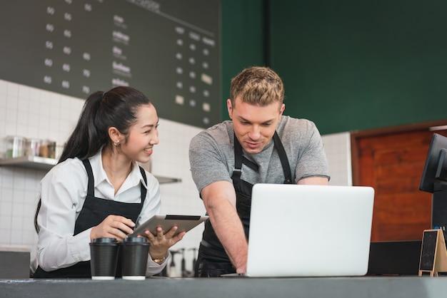 カフェのオーナーとバリスタが、コーヒーでコンピュータータブレットで顧客からのオンライン注文をチェックしている