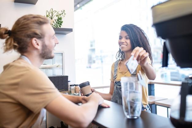 Кафе, оплата. улыбающаяся длинноволосая женщина-мулат с кофе, держащая банкноту в руке, и довольный мужчина в фартуке за прилавком