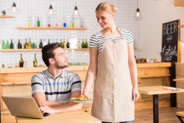 카페 서비스. 그에게 음식을 제공하는 동안 웃고 그녀의 고객을보고 기쁘게 좋은 긍정적 인 여자
