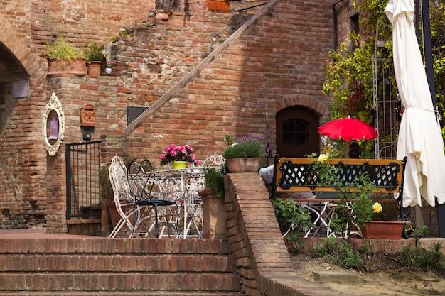 Кафе. небольшой дворик. столы и стулья в городе италия, чертальдот. тоскана, италия