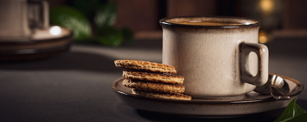 Cafe surface with brown cup of coffee and dutch traditional cookies stroopwafels. retro style toned. banner