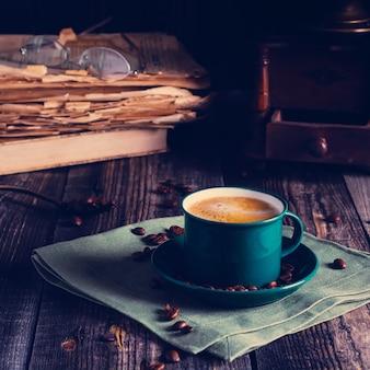 リネンナプキンの上に立っているエスプレッソコーヒーの緑のカップとカフェテーブル