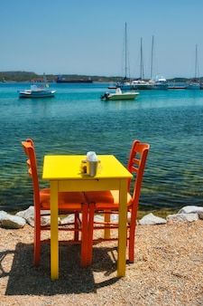 Cafe tableon beach in adamantas town on milos island with aegean sea with boats in background