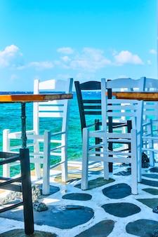그리스 미코노스 섬의 물 근처 카페 테이블과 의자