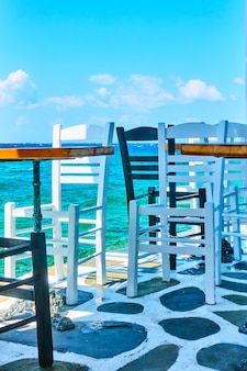 Cafe tables and chairs near water in mykonos island, greece