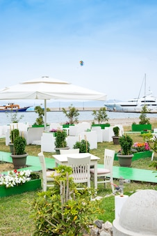 Cafe tables served with a white tablecloth near the sea coast for relaxing holidays vacations