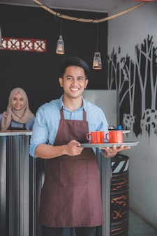 Cafe waiter holding tray with two cup of coffee