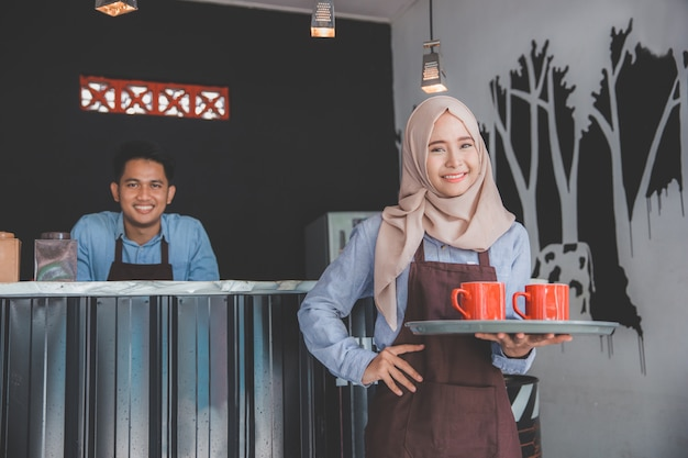 Cafe waiter holding tray with two cups of coffee