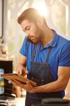 Официант кафе разговаривает по телефону с клиентом и вводит информацию о заказе на планшетный компьютер