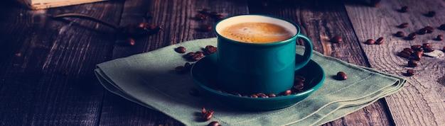 レトロなコーヒーグラインダーの古い本とリネンナプキンの上に立っているエスプレッソコーヒーの緑のカップとカフェ