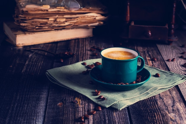 Cafe with a green cup of espresso coffee standing on a linen napkin with a retro coffee grinder old book