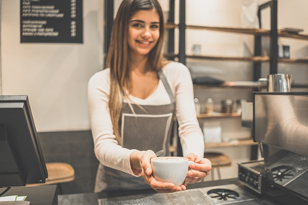 The cafe worker holding a cup of coffee