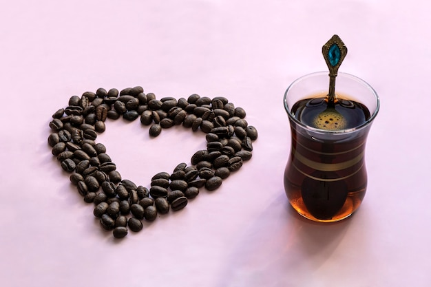 カフェやレストラン。ハート型のコーヒー豆が入った爽快なブラックコーヒーのマグカップ。碑文の場所。ホットドリンクと愛の概念。