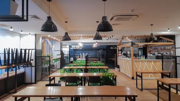 Кафетерий, столовая без людей с деревянными столами и зелеными стульями. интерьер с элементами из дерева и металла. современные обеденные зоны с оконным освещением. украина, киев - 19 февраля 2021 года.