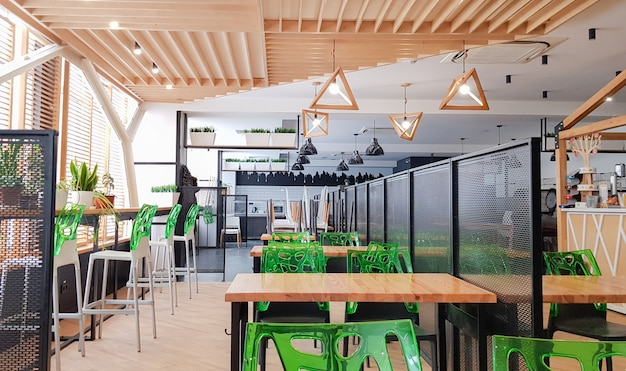 Cafeteria, no people dining room with wooden tables and green chairs. interior with wood and metal elements. modern dining areas with window lighting. ukraine, kiev - february 19, 2021.