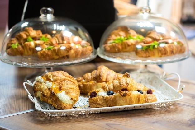 Поднос в кафетерии с домашними булочками и круассанами. свежая аппетитная выпечка.