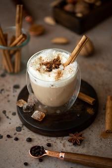 ホイップクリーム、シナモン、アニスをグラスに入れたカフェラテ