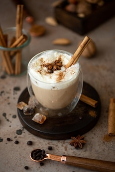 Caffe latte with whipped cream, cinnamon and anise in a glass