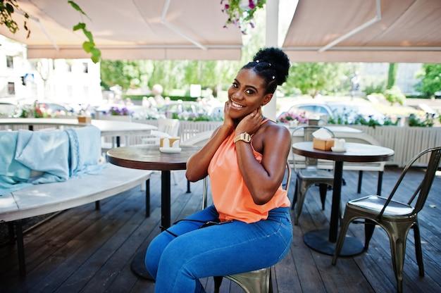 Афро-американская девушка сидя на таблице caffe и представила.
