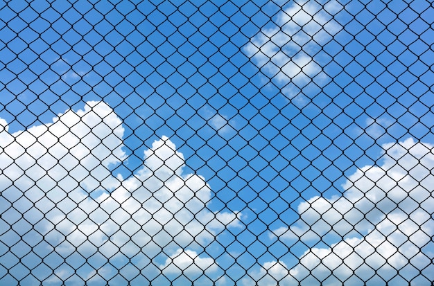 Cage metal wire on blue sky with cloud in summer - background