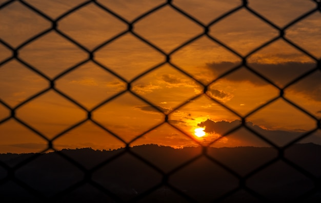 Cage with the evening sky, the concept of lack of freedom.