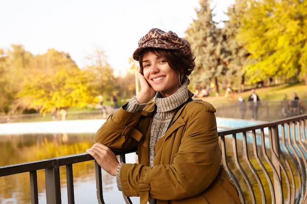 ボブの髪型で頭を上げた手に寄りかかって、ぼやけた公園の上に立って、明るい笑顔で前向きに見ている陽気な若いブルネットの女性