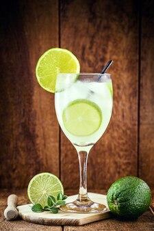 Caipirinha, 나무 배경에 cachaã§a (브라질 럼)와 브라질 레몬 음료