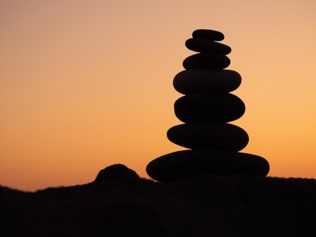 Пирамида из камней на закате, каменные весы, пирамида из камней на закате, концепция жизненного баланса, гармония и медитация