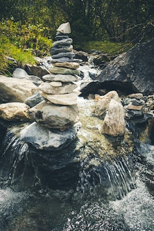 Cairn on a river in vanoise national park valley, savoy, french alps