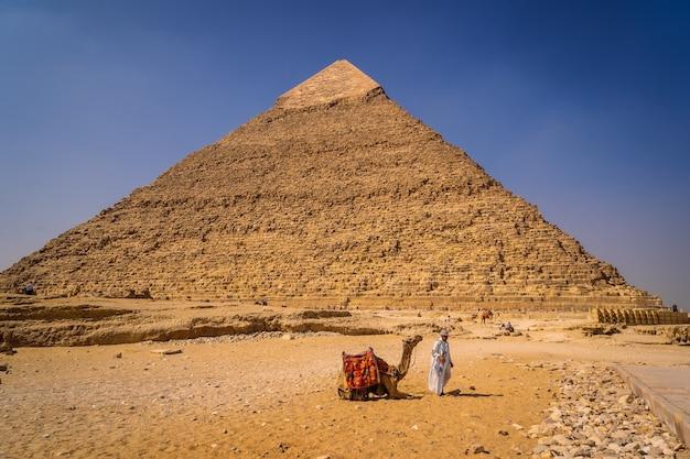 カイロ、エジプト; 2020年10月:カフレンのピラミッドに男と一緒に座っているラクダ。ギザのピラミッド世界最古の葬式の記念碑