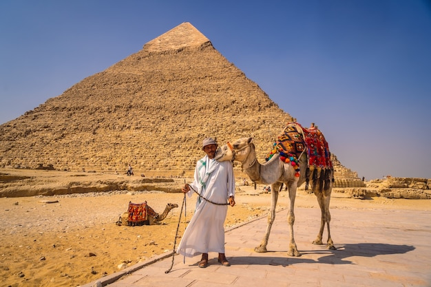 Cairo, egypt; october 2020: a local vendor with his camel at the pyramid of kefren. the pyramids of giza the oldest funerary monument in the world