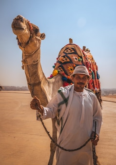 Cairo, egypt; october 2020: portrait of a local vendor with his camel at the kefren pyramid. the pyramids of giza the oldest funerary monument in the world