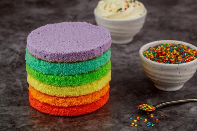 ケーキの組み立て。白いアイシングとふりかけのレイヤーケーキ。