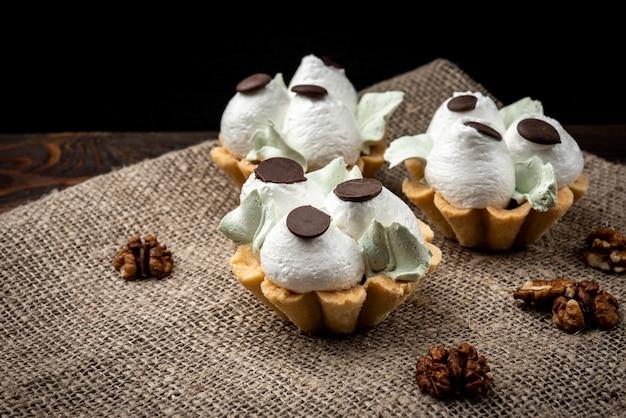 Корзины для торта со сливками на темном деревянном фоне.