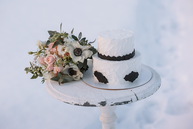 A cake in black and white design, standing on a stand in a winter forest on the snow.