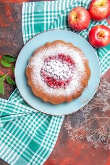 Una torta una torta con frutti di bosco mele sulla tovaglia bianco-azzurra