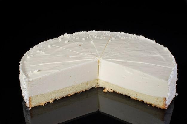 黒の背景に部分的にスライスされたケーキチーズケーキ