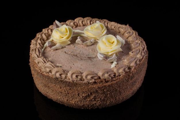 黒の背景にココナッツシェービングとケーキのクローズアップ