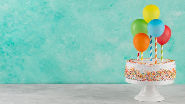 Cake and colorful balloons with copy space