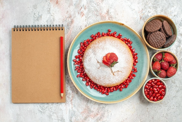 Cake cookies cake with strawberries next to the pencil notebook