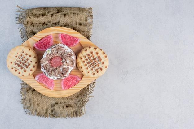 Una torta, biscotti e marmellate su un vassoio sul tavolo di marmo.