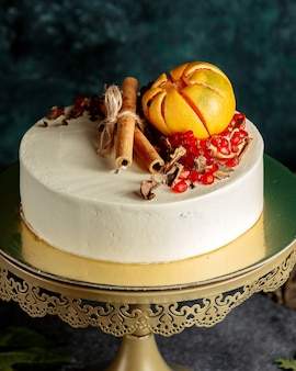 Cake covered with white cream and pomegranate, grapefruit and cinnamon sticks