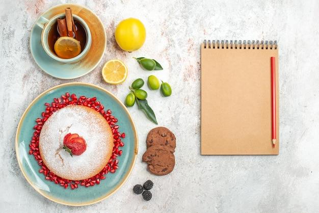 テーブルの上のイチゴとザクロの柑橘系の果物のクッキーとケーキのプレートの横にあるケーキクリームノートブック赤鉛筆