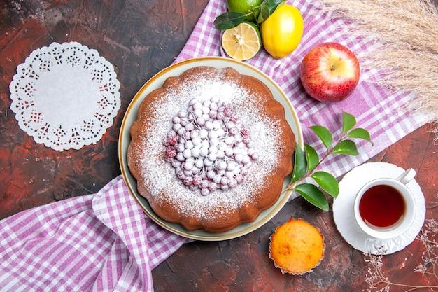 Una torta una tazza di tè una torta limoni sulla tovaglia cupcake alle mele centrino di pizzo
